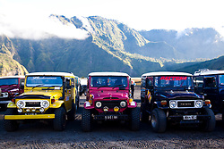 Jeeps for tourists visiting the crater wait on the plain beneath Mount Bromo in East Java, Indonesia, Southeast Asia