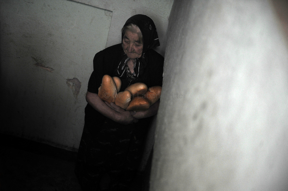 "An old Georgian woman, who fled her village after a Russian attack, carries bread inside the soviet-era defence ministry building where she took refuge, on September 3, 2008 in Tbilisi. The United States has a ""deep and abiding"" interest in the security of the Caucasus region, US Vice President Dick Cheney said as he toured Azerbaijan and Georgia."
