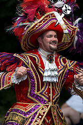 Philadelphia style colorful mummer marches and struts at parade.
