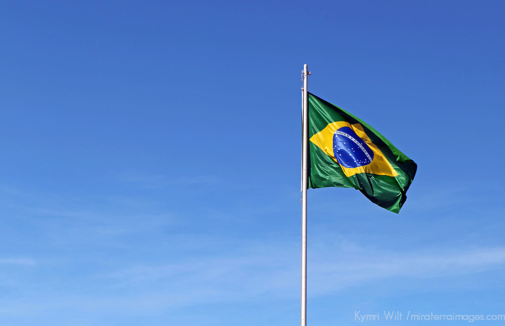 South America, Brazil, Brasilia.  The flag of Brazil waves against a blue sky.