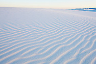 Warm light paints the gypsum sand patterns at sunset in White Sands National Monument, New Mexico