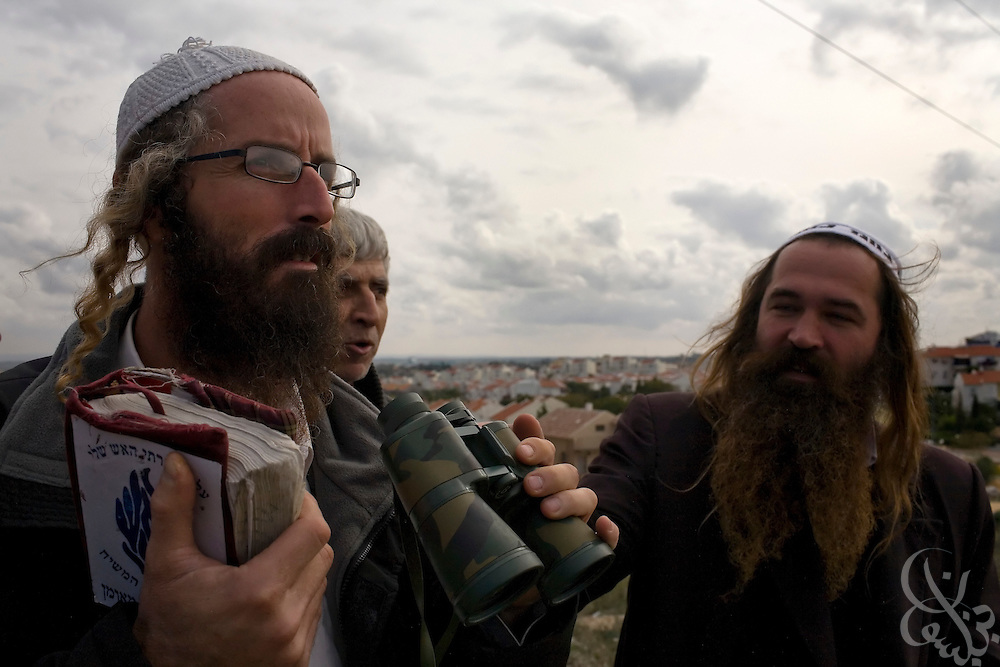 Israeli members of the Jewish Breslav Hassidim  watch the ongoing Israeli Defense Forces attack on nearby Gaza January 08, 2009 from a hilltop in Sderot, Israel. At times there is a circus-like atmosphere on the hilltops near Sderot overlooking Gaza as curious onlookers  and war tourists congregate to watch the ongoing military action less than a few kilometers away.