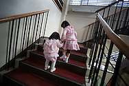 Yume Nakamaru (aged 4) helps her younger sister Hime (aged 2) on the stairs, as they enter Kawauchi community centre to join the School and kindergarten entrance ceremony, in Kawauchi, Japan on Friday 6th April 2012. Restrictions on residents living in, and visiting their homes and business in Kawauchi, have just been relaxed and approximately 533 people have moved back out of an original town population of 2,856. The residents initially left due to fears over high levels of nuclear radiation contamination from the explosions at the Fukushima Daiichi nuclear plant which is approximately 25-30km away from the town. The nuclear plant exploded in the aftermath of the earthquake and tsunami which hit the Tohoku coastline on 11th March 2011.