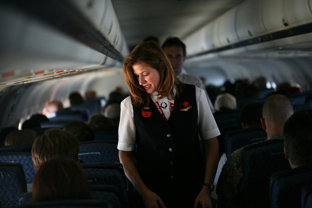 American Airlines flight attendant Kristen Heller walks down the plane doing a routine cabin check during American Airlines flight 366 from Minneapolis to Chicago October 30, 2010.  (Courtney Perry/The Dallas Morning News) **for slideshow**