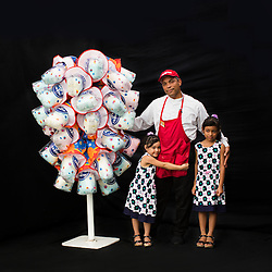 Portrait of concession worker Milciades Jiminez with his daughters Allison and Alina.<br /> <br /> Ringling Bros. and Barnum &amp; Bailey Circus started in 1919 when the circus created by James Anthony Bailey and P. T. Barnum merged with the Ringling Brothers Circus. Currently, the circus maintains two circus train-based shows, the Blue Tour and the Red Tour, as well as the truck-based Gold Tour. Each train is a mile long with roughly 60 cars: 40 passenger cars and 20 freight. Each train presents a different &quot;edition&quot; of the show, using a numbering scheme that dates back to circus origins in 1871 &mdash; the first year of P.T. Barnum's show.