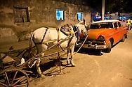 Horse and old car at night in Santiago de Cuba, Cuba.