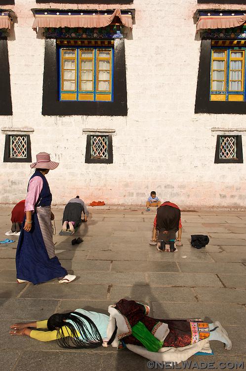 Tibetan Buddhist pilgrims prostrate themselves before The Jokang, Tibet's most holy monastery, in Lhasa, Tibet.