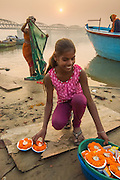 Girl selling candles with flowers for Ganga Aarti ceremony; make a wish, light a candle, and set it afloat on the Ganges, Varanassi, India.