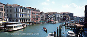Panoramic photo/foto of the Grand Canal (Canal Grande) viewed from the Rialto Bridge.   This view of the canal includes the quayside, a vaporetto, a gondola in the middle of the canal, and a clear view of two palazzos, Palazzos Bembo and Manin-Dolfin against a blue stky with summery clouds. Travel photo of Venice, Italy by Tomoko Yamamoto. Original on 120 slide film taken with Mamiya 6 (Medium Format). High-resolution file of 100 MB:<br /> 8880x3804 pixels 96.6 Mb TIFF;29.6x12.7 inches or 75x32cm at 300 dpi color; <br /> 24 Mb JPEG<br /> <br /> Unsharpened file available. Contact the photographer for details.<br /> <br /> Panoramaaufnahme, Panoramabild im Mittelformat auf dem Canal Grande aus der Rialtobr&uuml;cke in Venedig, Italien.  Venezia, Italia