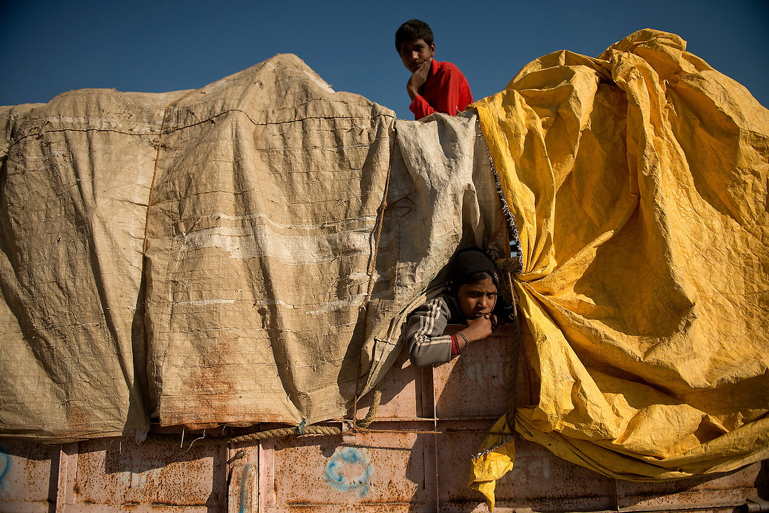 A couple of boys watch the busy streets of the vast Kumbh Mela tent city from on a trailer on February 7, 2013 in Allahabad, India. — © Jeremy Lock/
