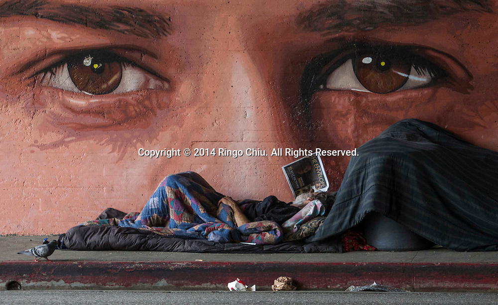 A homeless man reads newspaper in front of a mural painted by artist Ruben Soto on Friday, Feburary 7, 2014, in Los Angeles. (Photo by Ringo Chiu/PHOTOFORMULA.com)