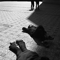 Watched over by police two anti-America and anti-Iraq war protestors lie in the sunshine, unable to proceed to their destination of the American embassy. Tokyo, Japan.