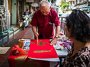 "18 JANUARY 2017 - BANGKOK, THAILAND: A woman watches a traditional Chinese calligrapher write out New Years greetings in Bangkok's Chinatown district, before the celebration of the Lunar New Year. Chinese New Year, also called Lunar New Year or Tet (in Vietnamese communities) starts Saturday, 28 January. The coming year will be the ""Year of the Rooster."" Thailand has the largest overseas Chinese population in the world; about 14 percent of Thais are of Chinese ancestry and some Chinese holidays, especially Chinese New Year, are widely celebrated in Thailand.       PHOTO BY JACK KURTZ"