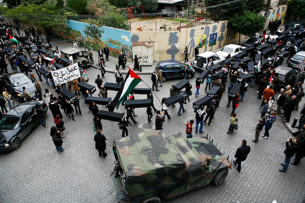 As Israel continued its aerial assault on the Gaza Strip for the seventh consecutive day, Lebanese and Palestinian refugees in Lebanon took to the streets of Beirut to protest the ongoing attacks. The demonstration started in Beirut's Hamra neighborhood and marched a few kilometers to the Egyptian Embassy in Lebanon where protestors were stopped from advancing by rows of barbed-wire and dozens of riot police. The demonstrators marched carrying dozens of coffins draped in black cloth representing the over 400 Palestinians killed by Israeli air strikes in Gaza.