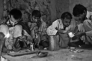 Pashtun men smoke heroin in the entrace to a deralict home in Peshawar..Record opium crops in neighbouring Afghanistan have resulted in a cheap, affordable and plentiful supply of heroin and opium in Pakistan...In the frontier town of Peshawar, a gram of heroin sells for 100 rupees, little more than a dollar. Most addicts smoke or ?chase the dragon?, some inject but the inaccessibility of syringes dictate most addicts smoke the drug...Opium can be found in its pure form, fresh from record harvests in Afghanistan. Most is processed into heroin in the many factories along the Afghan / Pakistan borer, but some is retained, especially in the tribal province, for ?traditional medicinal? purposes such as bile din tea for curing arthritis and flu symptoms....