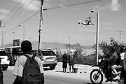 Haitians watch helicopters bearing supplies land at the Toussaint L'Ouverture airport in Port-au-Prince.