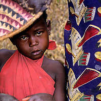 Africa, Kenya, Maasai Mara. A young Maasai boy peeks out with wondering eyes from a craft market display in his boma.