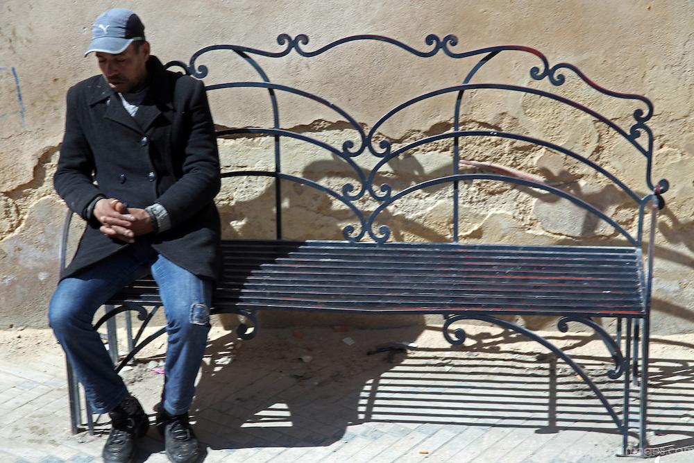 Africa, Morocco, Fes. Man sittingon bench, Fes.