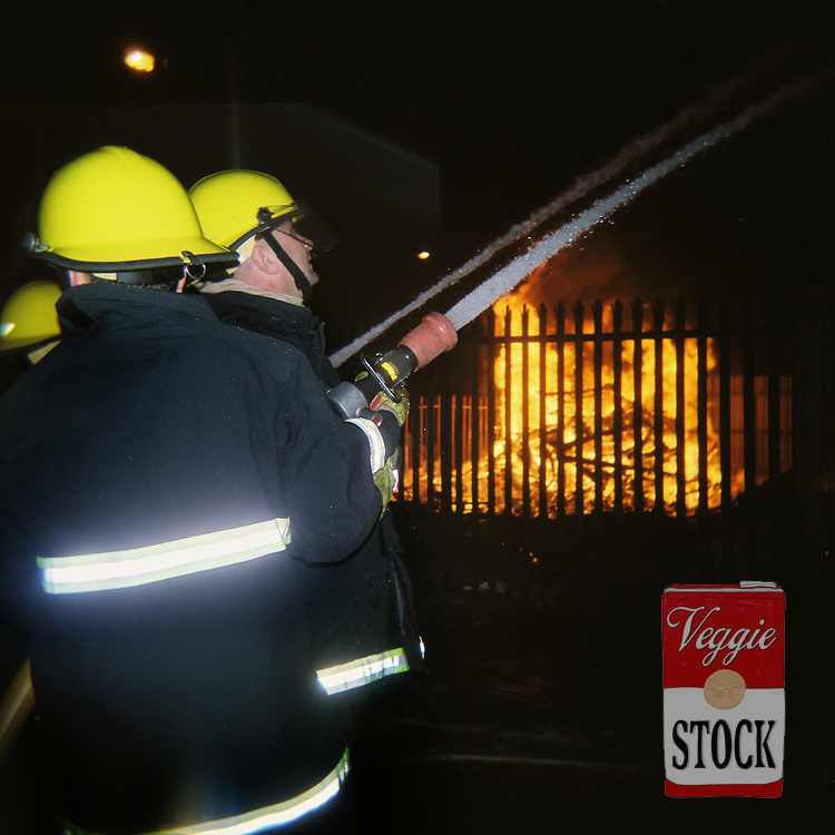 Firefighters try to prevent a house (graffitied with UFF) going on fire next to a bonfire in Belfast, Northern Ireland, July 2008. It was widely reported the next day that many firefighters were attacked and assaulted during the night. The bonfires are built in preparation for the annual 12th July celebrations, which commemorate the defeat of James Stuart at the Battle of the Boyne in 1690.