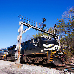 "A southbound Norfolk Southern freight train rumbles through an old Southern Railway-style signal bridge and over a ""Dragging Equipment Detector"" at Glenmary, TN."
