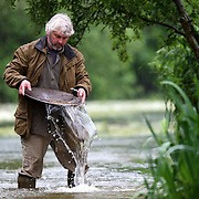 """VINCE THURKETTLE PANNING IN A RIVER IN NORFOLK...Britain is experiencing a gold rush with record numbers turning to prospecting to beat the credit crunch...Full-time gold-panner Vince Thurkettle said more people than ever before are heading to the UK's rivers in search of precious nuggets and flakes...Demand for his gold-panning courses has more than trebled in the last year driven by the deepening recession and the high price of gold...""""In the last 12 months people have suddenly shown much more interest in buying, selling and finding gold,"""" he said...""""Before a lot of people didn't seem to believe there was gold to be found in Britain's rivers...""""But now everyone knows the price of gold has gone up and suddenly due to the credit crunch more people are trying their hand at gold-panning.""""..The UK's last gold rush was in Kidonnan in Scotland in 1869 when a gold-panner struck lucky in the River Helmsdale...Within months hundreds of hopefuls had descended on the normally deserted Scottish Glen...But the prospectors left within three years and for decades gold-panning in Britain was seen by most as merely a hobby...Now adventurers in need of extra cash are once more heading to the hills of Scotland and Wales in search of treasure...SEE COPY CATCHLINE Britain's gold rush"""