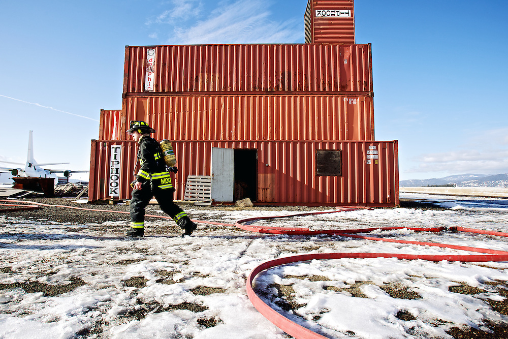Northern Lakes firefighter Cody Moore walks in front of his fire department's training tower constructed of metal shipping containers at the Coeur d'Alene Airport during a training session Wednesday.