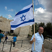 An Israeli man holding an Israeli flag walks outside the Dasmascus gate on Oct. 8, 2015. <br /> Photo by Olivier Fitoussi.
