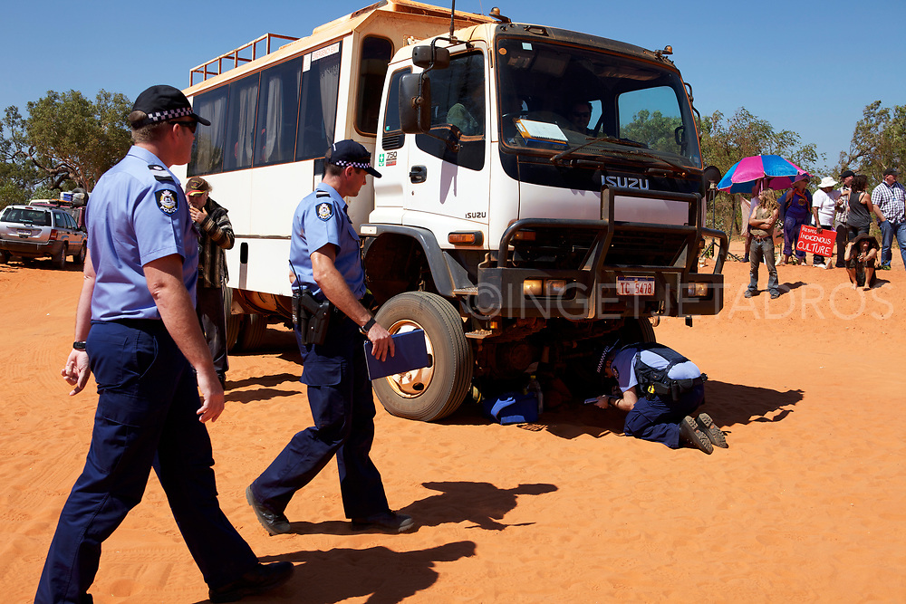 A protester, who has locked himself under a truck  is receiving a fine by the police on  the 100th day of the No Gas Protest at the Manari Road Community Camp in Broome, WA