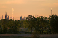 An oil refinery's cracking towers burn high in the sky at a refinery near Joliet, IL.