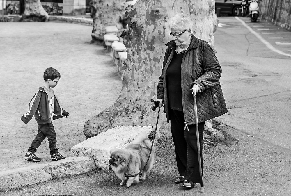 Young and old, unaware of each other. Saint Paul village, France.
