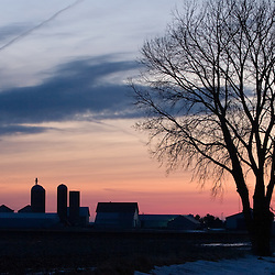 It's several tall silos and large barn silhouetted by the colorful winter sunset, the farm is all quiet on this cold day.