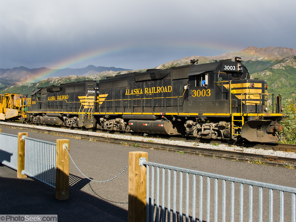 A colorful rainbow arches over Alaska Railroad train engines. The Alaska Railroad carries both freight and passengers from Whittier and Seward to Anchorage, Denali National Park, Fairbanks, Eielson Air Force Base, and Fort Wainwright in Alaska, USA. The railroad is connected to the lower 48 via three rail barges that sail between the Port of Whittier and Harbor Island in Seattle, Washington.
