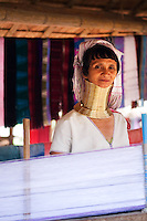 Woman from the Padaung long neck hill tribe weaving and wearing traditional dress near Tha Ton, Chiang Mai Province, Thailand