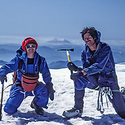 Friendly climbers atop Mount Rainier pose with Mount Saint Helens, in Washington, USA. For licensing options, please inquire.