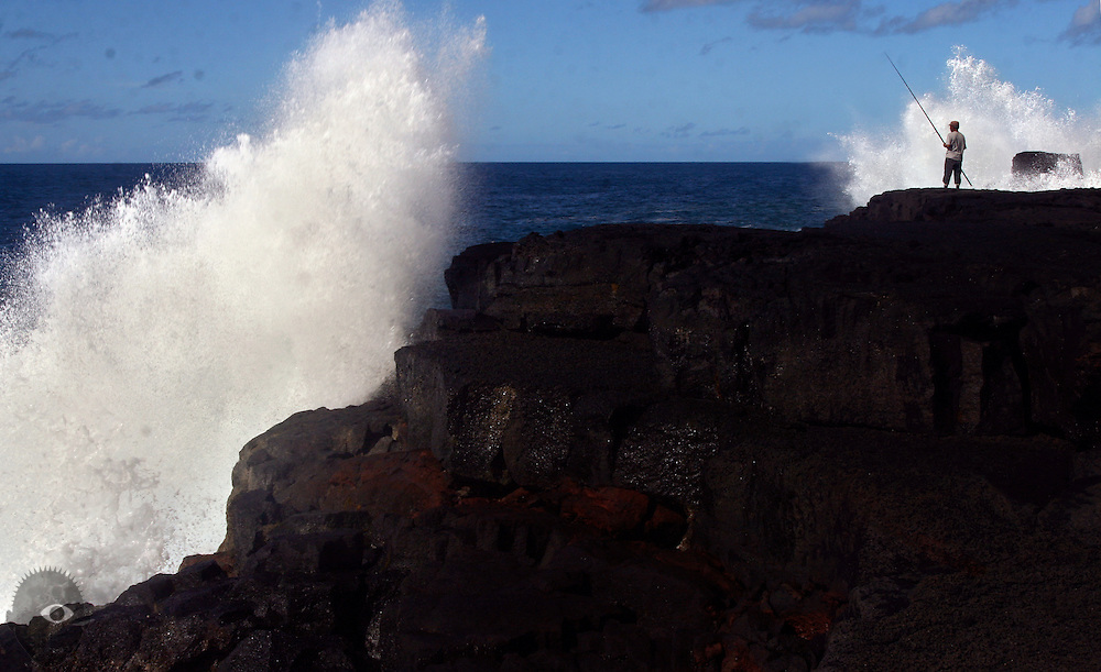 A fisherman holds his ground as big waves crash into the high cliff walls about MacKenzie State Park on the southeast side of the Big Island.