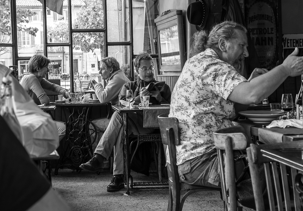 One setting- three stories. The man in the foreground conveys his excitement with his hand gestures. Obllivious to the rest of the world, the man in the middle, maybe a tourist,  just enjoys leisurely reading his book and sipping his drink. The women in the background are engaged in a very personal talk, reflective of the intimate atmosphere of this cafe. L'Isle-sur- la-Sorgue, Provence, France.