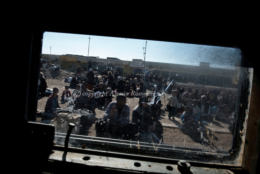 Iraq, Gogjali: Iraqi families, who fled the fight against jihadists of the Islamic State group in the city of Mosul, are seen through an armoured vehicle window as they wait to board a truck before heading to camps housing displaced people on November 2, 2016 near Gogjali, which lies on the eastern edge of Mosul. Alessio Romenzi