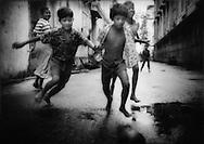 Boys playing on futbol on a Rangoon side street, Burma.