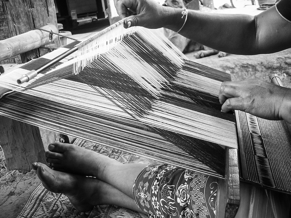 Weaving, Thailand, by Mida. <br /> <br /> Mira is from the Karen village located in the Mae Wang district of Northern Thailand. She spends most of her time in her village where she can be with her son, Warinton. Her mother, Si Taun, and the other women of the village spend most of their time weaving scarves and other items, which can be sold to western tourists.<br /> <br /> This photograph shows Mida&rsquo;s mother, weaving traditional Thai Karen fabric. She is forty-one years old. Weaving is a family tradition. Both Mida and her mother learned to weave when they were eight years old. Weaving is important to Thai Karen culture, and only the women weave.