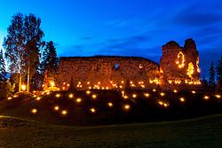 Vastseliina Bishop Castle Ruins in night with burning torches, Estonia