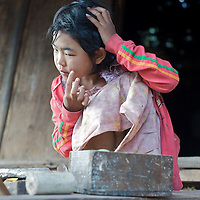 Tanaka is a special cream made from wood which is applied to keep the skin soft and for protection from the sun.  Here a young girl applies the cream on the front porch of her home in Ywapu Village near Kalaw, Myanmar.