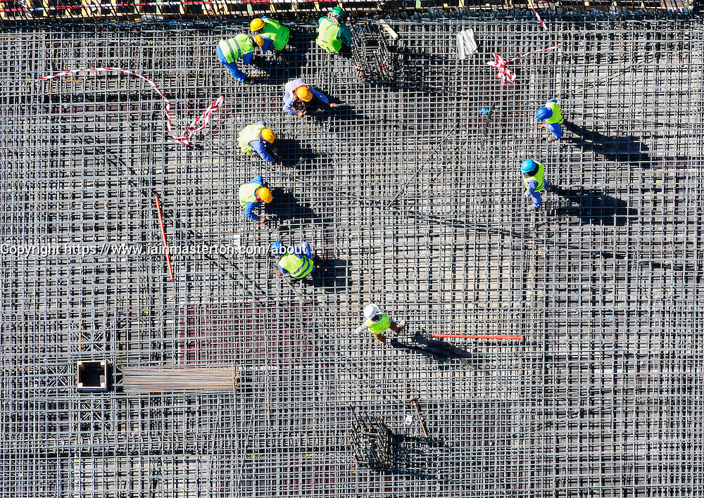 Migrant workers on construction site of apartment skyscraper tower in Dubai United Arab Emirates