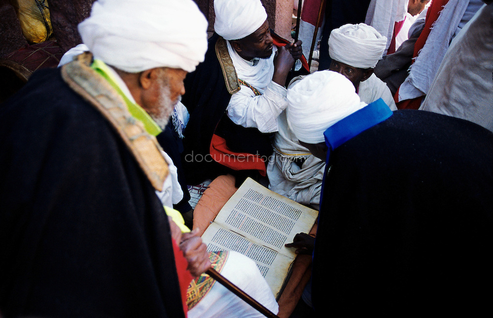 On Christmas morning, after mass, a group of priests and deacons are reading a very old bible. The bible is written in Ge?ez ? an ancient language which was used in North Ethiopia (AXUM), today only the church uses it, like Latin for the Catholic Church. The old man on the left is the priest of Bet Mariam; he is one of the most important priests in Lalibela.