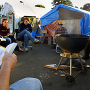 Bible study and hot dogs make a good combination for dinner at Dignity Village in Portland, OR. There are now 65 homeless people who have taken up residence on the leaf recycling land near the airport with the city's permission. They are being asked to leave again by October and find a new home.