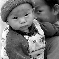 A young boy glances hiding behind his baby brother.