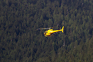 Helicopter with Talon Helicopters leaves the North Shore Rescue helipad on Capilano Road in North Vancouver.  Photographed from Capilano River Regional Park (Cleveland Dam) in North Vancouver, British Columbia, Canada.