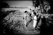 Squatter boys at Phnom Penh city dump head off to school in the morning, Cambodia.  Boys must then return home and study in the midst of the ever-present stench of rotting garbage.