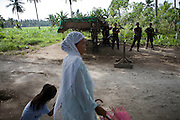 A Muslim woman and her daughter pass by members of the Moro Islamic Liberation Front (MILF) at their camp at Darapanan, outside of Cotabato Ciy in Mindanao. Skirmishes between the MILF and Armed Forces of Philippines (AFP) have continued in Lanao del Norte and Sarangani regions of Mindanao...