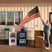 USA, Washington, Coulee City, Shopkeeper puts up American flag outside gas station at sunrise on spring morning