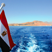 Egypt's flag in the Red Sea and Sinai mountain on background